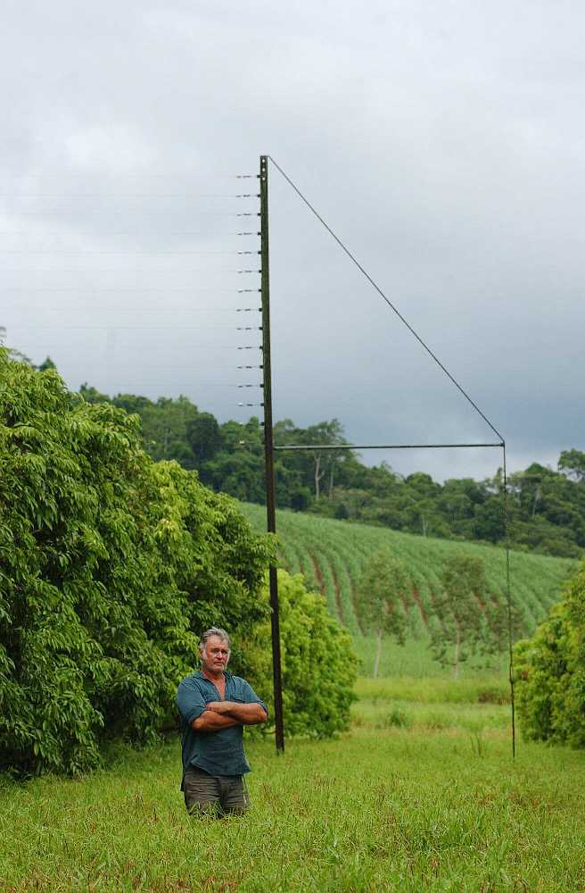 Dick Yardley standing in front of part of the electric grid on his farm Photo: Cairns Post, 2006