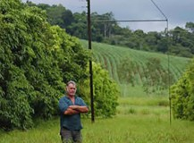 Dick Yardley standing in front of part of the electric grid on his farm