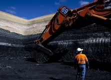 Worker at base of Alpha test pit in 2011. The obvious white layer in the black coal seams is the C-D sandstone, one of the aquifers to be heavily impacted by the proposed mine. Source: GVK / Courier Mail